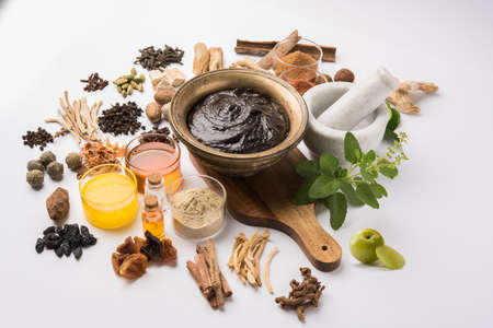 Top view of a bowl of Chyawanprash, an Indian Ayurvecid dietary supplement, with the ingredients laid around it, on a white background.