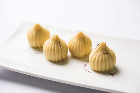 A modak is an Indian sweet dumpling popular in India. It is called modak, Kozhakkatta, modhaka, kadubu, modhakam, kozhakkattai, kudumu. made up of coconut and jaggery, rice flour, wheat with khava Banco de Imagens - 80835528