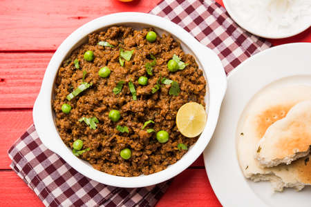 Indian Masala Kheema Pav or khima or Dry Spicy Minced Meat usually served with indian flat bread called kulcha/roti/chapati, garnished with green peas. Selective focus Archivio Fotografico