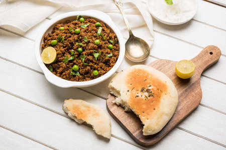 Indian Masala Kheema Pav or khima or Dry Spicy Minced Meat usually served with indian flat bread called kulcharotichapati, garnished with green peas. Selective focus Stock Photo