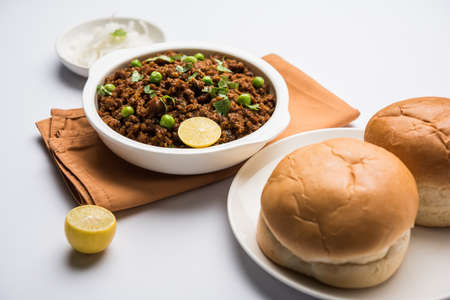 red onions: Indian Masala Kheema Pav or khima or Dry Spicy Minced Meat usually served with indian flat bread called kulcharotichapati, garnished with green peas. Selective focus Stock Photo