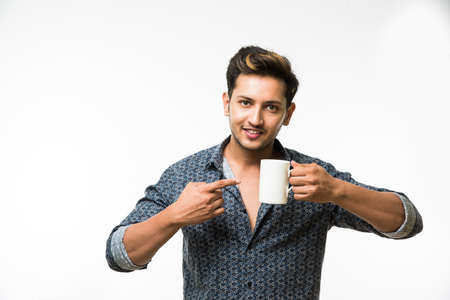 salud sexual: Portrait of a Young handsome Indian man having a cup of coffee, standing isolated over white background
