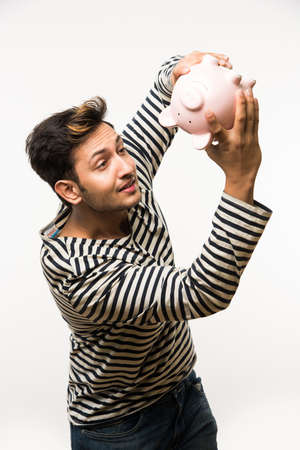 rupees: India and finance concept - Handsome Indian man or boy holding pink piggy bank, with different expressions holding indian currency notes of 2000 and 500 or rupee coins, standing over white background Stock Photo