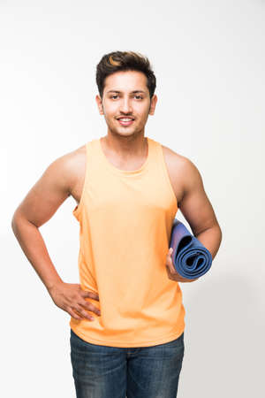 Good looking Indian young man holding yoga or exercise mat and having a sip of fresh juice in a glass post exercise or yoga  asana, isolated over white background Stock Photo