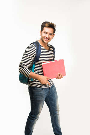 Handsome and young indian Male college student carrying bag on white background while holding college books, laptop or smart phone Фото со стока - 82493769