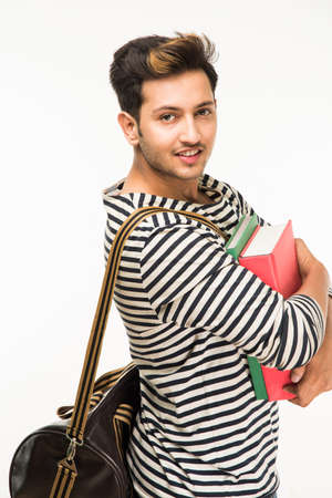 carrying: Handsome and young indian Male college student carrying bag on white background while holding college books, laptop or smart phone