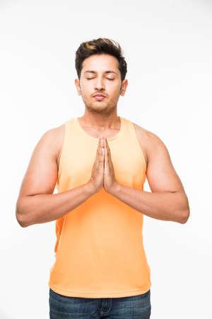 Handsome indian man or boy holding both hands together in Namaskara  namaskaram  pranam pose or mudra while wearing trendy looking orange sleev less T-shirt, standing over white background