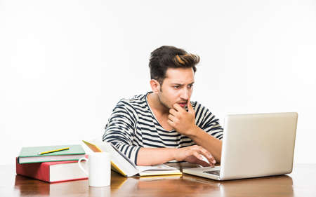 Handsome Indian Boy Or Male College Student Studying On Study Table With  Pile Of Books,
