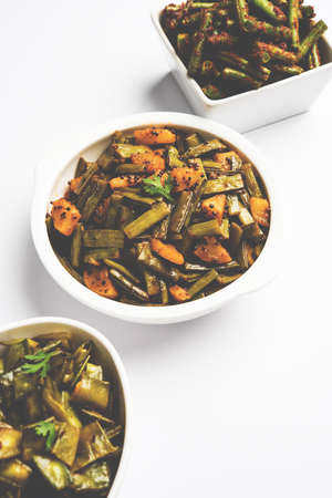 long bean: Closeup picture of indian green vegetable masala curry  sabzi  sabji like Green Beans, gowar cluster beans and bhindi or ladies finger or okra. Served in white ceramic bowl over white background. Stock Photo