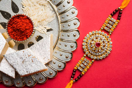 Raksha Bandhan greeting - Rakhi and gift with sweet kaju katli or mithai and rice grains & kumkum in a decorative plate. Traditional Indian wrist band is a symbol of love between Brothers and Sisters