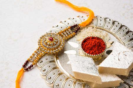 Raksha Bandhan begroeting - Rakhi en cadeau met zoete kaju katli of mithai en rijstkorrels & kumkum in een decoratieve plaat. Traditionele Indische polsband is een symbool van liefde tussen broers en zussen