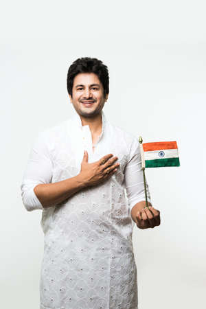 Indian handsome boy or man in white ethnic wear holding indian national flag and showing patriotism, standing isolated over white background