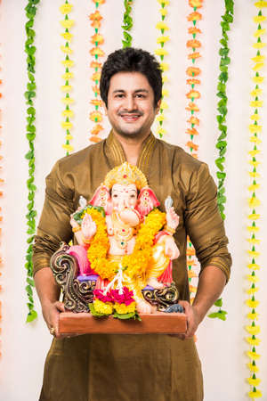 Indian handsome man in ethnic wear holding a Ganesh idol, welcoming God on Ganesh Chaturthi  festival at home with happy expressions