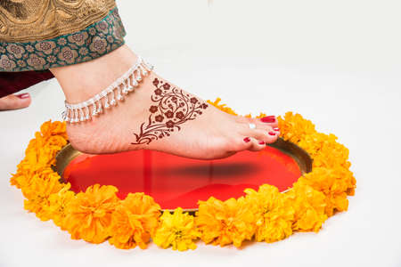 Gruha Pravesh  Gruhapravesh  Griha Pravesh, closeup picture of right feet of a Newly married Indian Hindu bride dipping her fit in a plate filled with liquid kumkum then stepping in husbands house