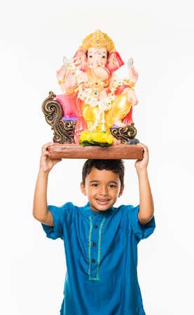 Portret van schattige kleine Indiase jongen met een Ganesh idool of heer Ganesha of Ganapati murti  standbeeld boven zijn hoofd, meenemen naar huis op Ganesh Chaturthi, geïsoleerd op witte achtergrond Stockfoto