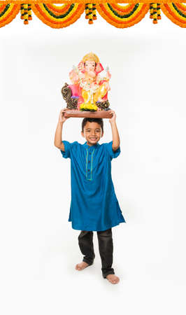 Portrait of cute little Indian boy holding a Ganesh idol or lord ganesha or ganapati murti statue over his head, taking home on Ganesh Chaturthi, Isolated over white background