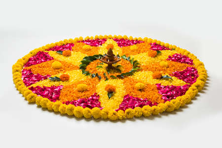 flower rangoli for Diwali or pongal made using marigold or zendu flowers and red rose petals over white background with diwali diya in the middle, selective focus
