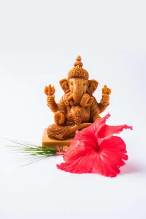 Happy Ganesh Chaturthi Greeting Card showing photograph of lord ganesha idol, pooja or puja thali, bundi laddumodak, durva and hibiscus or jasvand flower