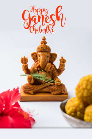 Happy Ganesh Chaturthi Greeting Card showing photograph of lord ganesha idol, pooja or puja thali, bundi laddumodak, durva and hibiscus or jasvand flower