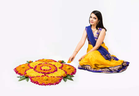 Indian woman or young girl making floral or flower rangoli for diwali or onam, isolated over white background Stock Photo