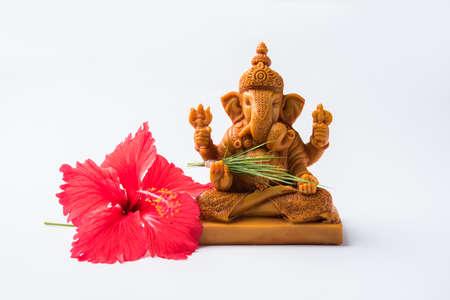 Happy Ganesh Chaturthi Greeting Card showing photograph of lord ganesha idol, pooja or puja thali, bundi laddu/modak, durva and hibiscus or jasvand flower