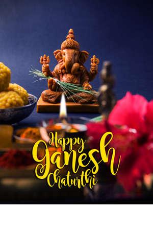 maharashtra: Happy Ganesh Chaturthi Greeting Card showing photograph of lord ganesha idol, pooja or puja thali, bundi laddumodak, durva and hibiscus or jasvand flower
