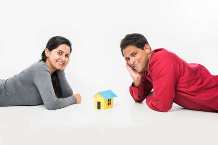 stock photo showing side angle of Indian or asian smart and cheerful  happy couple holding 3D paper house model and sitting isolated over white background, asian couple and real estate concept.