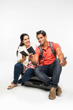 indian couple sitting over packed suitcase, waiting for departure with passports in hand or taking selfie. isolated over white background Zdjęcie Seryjne