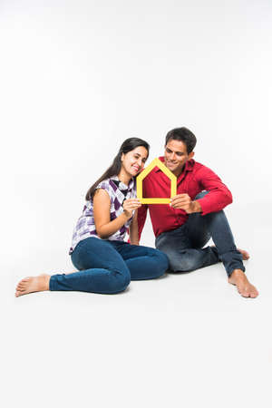 stock photo showing side angle of Indian or asian smart and cheerful / happy couple holding 3D paper house model and sitting isolated over white background, asian couple and real estate concept.