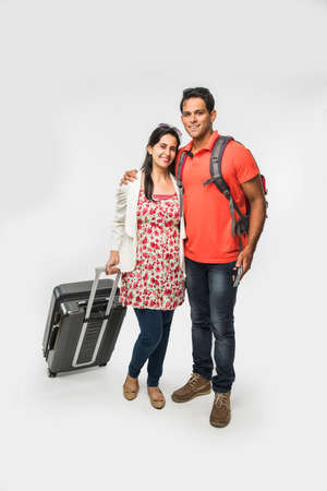 stock photo of smart Asian or Indian couple traveler with suitcase and hike bag isolated over white background, going abroad or within country, perfect shot for tours and travels company