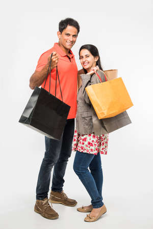 Indian happy and Young couple with shopping bags, asian man and women holding shopping bags, isolated over white background Archivio Fotografico