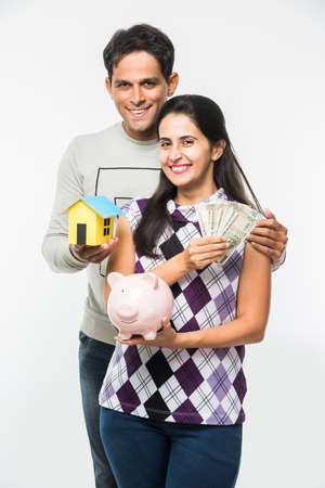 rupees: Indian smart and cheerful  happy couple holding currency notes, Pink Piggy bank and 3D paper house model isolated over white background, asian couple and real estate
