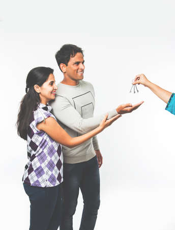 stock photo showing Indian couple who just rented or purchased new home or car. Man and woman are happy to receive keys for newly rented apartment or car