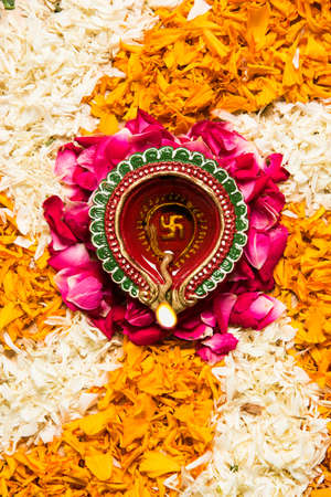 flower rangoli for Diwali or pongal or onam made using marigold or zendu flowers and red rose petals over white background with diwali diya in the middle, selective focus Stock Photo - 85066807