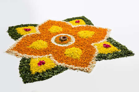 religious event: flower rangoli for Diwali or pongal or onam made using marigold or zendu flowers and red rose petals over white background with diwali diya in the middle, selective focus
