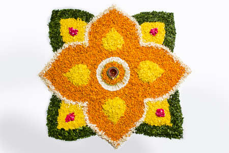 diwali celebration: flower rangoli for Diwali or pongal or onam made using marigold or zendu flowers and red rose petals over white background with diwali diya in the middle, selective focus