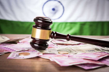 stock photo of Indian Currency Rupee Notes with Law Gavel isolated on white, concept showing indian finance law with paper currency of 500,2000 with gavel and indian flag Stock Photo