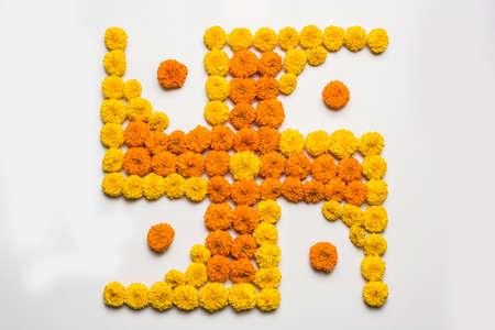 stock photo of hindu auspicious symbol called Swastika made using marigold flower or zendu or genda phool, Flower rangoli in the shape of Swastika for diwalipongalonam over white background