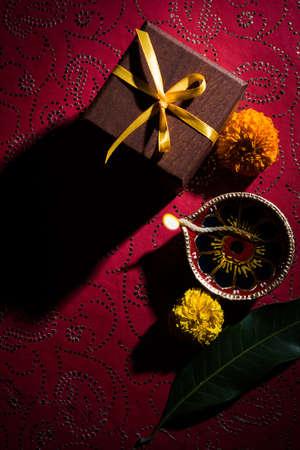 Foto de archivo de hermosa diwali diya con regalos y flores, sobre fondo decorativo, iluminación de mal humor y enfoque selectivo