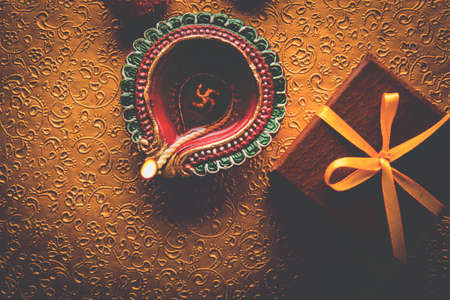 stock photo of beautiful diwali diya with gifts and flowers, over decorative background, moody lighting and selective focus