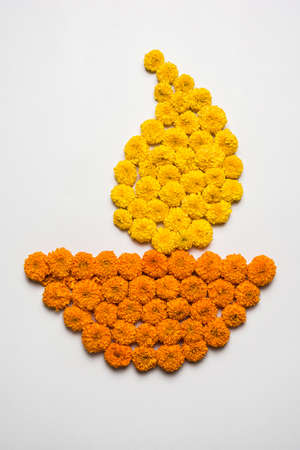 stock photo of marigold flower rangoli in shape of Diya. Diya made using flowers for diwali festival or for pongal or for onam over white background, selective focus