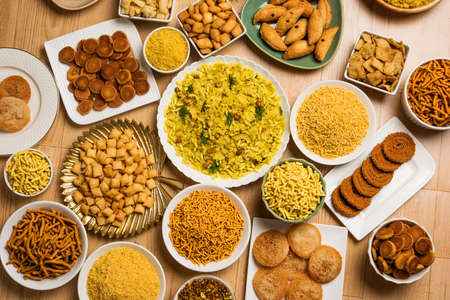 stock photo of  Diwali food or Diwali snacks or Diwali sweets like anarsa, bakarvadi, chakli, sev, bhujiya, shankar pale and chivda or chiwada, karanji, favourite indian diwali recipe, selective focus