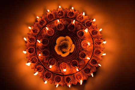 Stock Photo of an illuminated terra-cotta Diwali lamp or Diya with detailed artwork on it. on a moody background and selective focus Stock Photo
