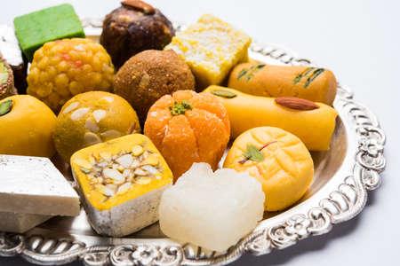 Foto de archivo de dulces indios servidos en plateado o plato de madera. variedad de Peda, burfi, laddu en placa decorativa, enfoque selectivo Foto de archivo