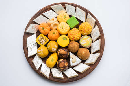 Foto auf Lager der indischen Süßigkeiten diente in der silbernen oder hölzernen Platte. Vielzahl von Peda, Burfi, laddu in der dekorativen Platte, selektiver Fokus
