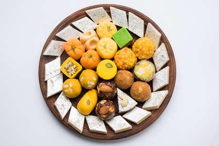 La foto di riserva dei dolci indiani è servita in piatto d'argento o di legno. varietà di Peda, burfi, laddu in piatto decorativo, messa a fuoco selettiva