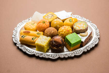 Stock photo of Indian sweets served in silver or wooden plate. variety of Peda, burfi, laddu in decorative plate, selective focus