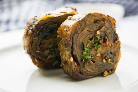 konkan: Patra or Paatra or Alu Vadi is a popular maharashtrian and Gujrati snack recipe made using colocasia leaves, rice flour and flavourings spices, tamarind, and jaggery, selective focus