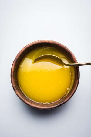 Ghee or clarified butter close up in wooden bowl and silver spoon, selective focus