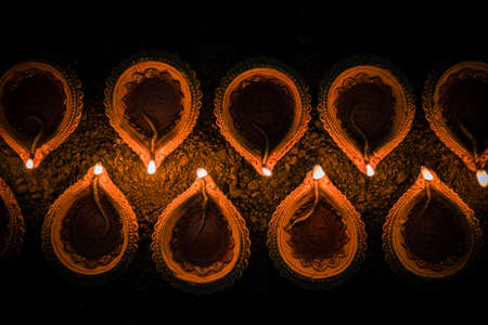 curve: Happy Diwali - many Terracotta diya or oil lamps arranged over clay surface or ground in one line or curved or zigzag form, selective focus